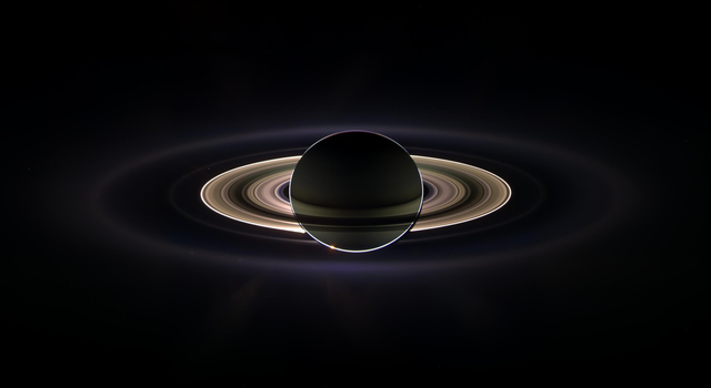 NASA's Cassini spacecraft created this panoramic view of the Saturn system, with Earth appearing as a pale blue dot, in 2006.