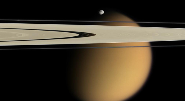 The blurring effects of Titan's aerosols are obvious in this image, where the orange moon peeks from behind two of Saturn's rings