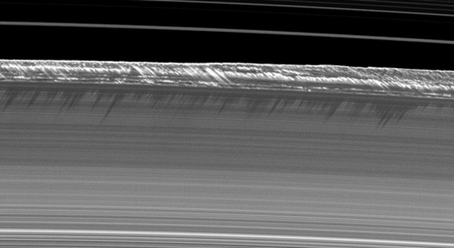 Vertical structures, among the tallest seen in Saturn's main rings, rise abruptly from the edge of Saturn's B ring to cast long shadows on the ring in this image taken by Cassini.