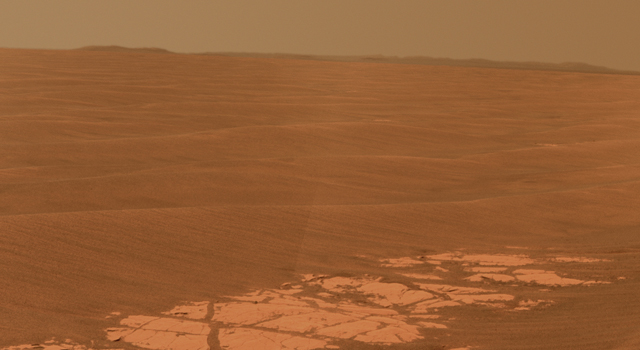 This image shows an outcrop of rocks at the foot of the rover and beyond these rocks rippled dunes
