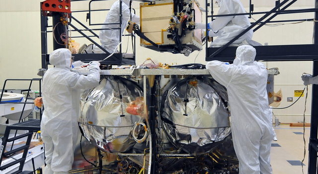 Workers place Juno's special radiation vault onto the propulsion module