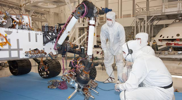 Test operators in a clean room at NASA's Jet Propulsion Laboratory, Pasadena, Calif., monitor some of the first motions by the robotic arm.