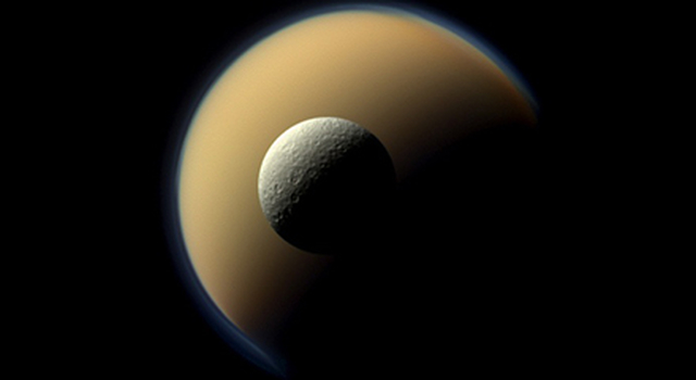 Saturn's largest and second largest moons, Titan and Rhea, appear to be stacked on top of each other in this true-color scene from NASA's Cassini spacecraft.
