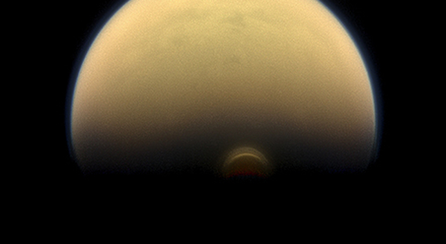 Slipping into shadow, the south polar vortex at Saturn's moon Titan still stands out against the orange and blue haze layers that are characteristic of Titan's atmosphere