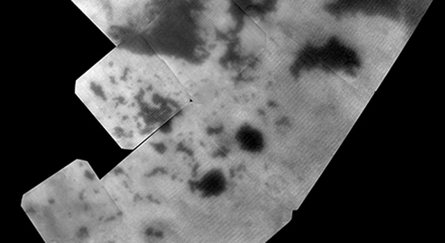 The vast hydrocarbon seas and lakes (dark shapes) near the north pole of Saturn's moon Titan sprawl out beneath the watchful eye of NASA's Cassini spacecraft
