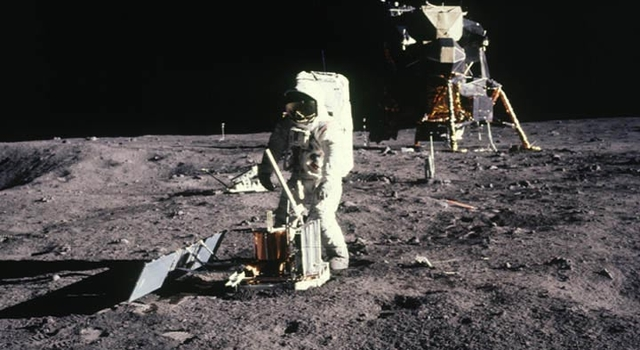 Astronaut Buzz Aldrin stands in front of a lunar reflector placed on the Moon