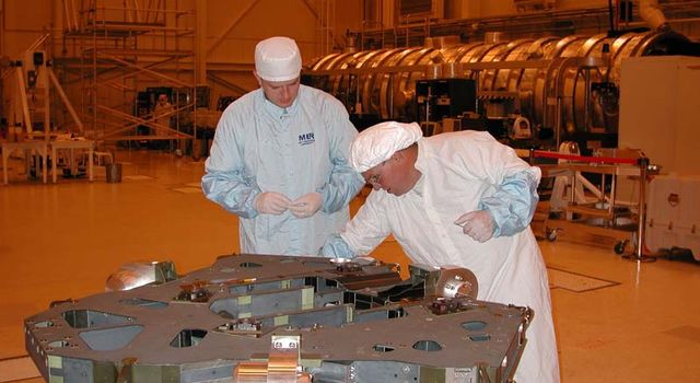 Engineers on the Mars Exploration Rover project make necessary adjustments to an engineering model of the rover.