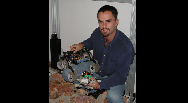 Gabe Sibley holds a spider-bot (front) and another robotic prototype