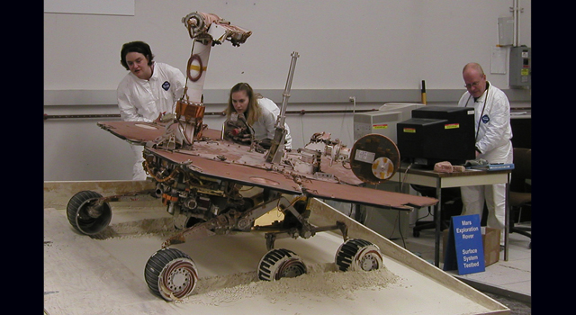 engineers study test rover in order to trouble-shoot Spirit's situation