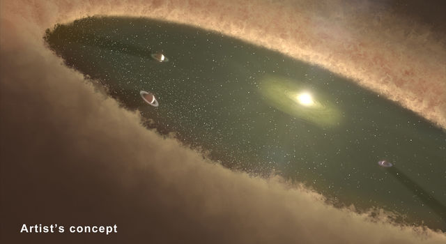 This artist's concept depicts giant planets circling between belts of dust.