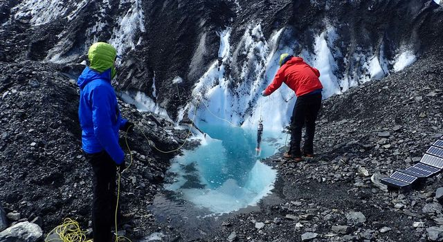 JPL engineers Andy Klesh and John Leichty lower a homemade probe into a moulin on Alaska's Matanuska Glacier.