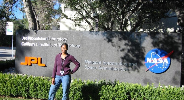 Tracy Drain stands by the JPL/NASA sign at JPL