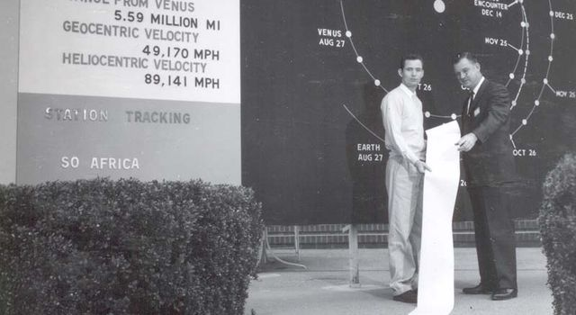A long scroll of data from Venus, seen in front of JPL's Mariner 2 mission board.
