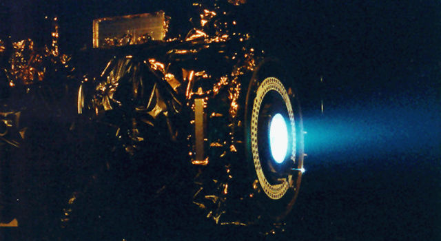 Photo of ion engine thrusting in a vacuum chamber at JPL.