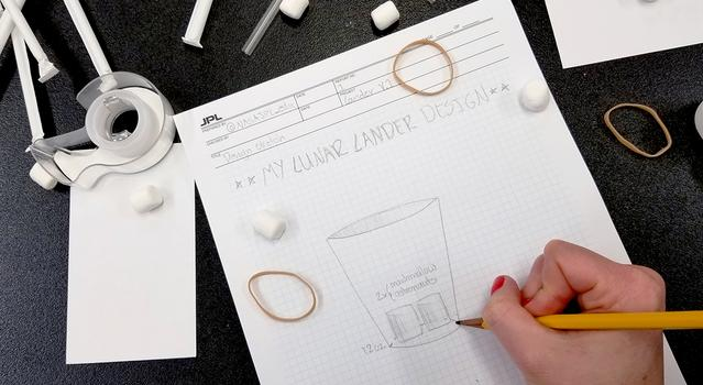Sketch of a lunar lander on graph paper with marshmallows, rubber bands and straws scattered around