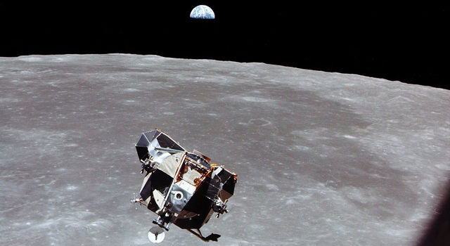 Image of the Apollo 11 lunar module flying above the Moon with the Earth visible in the distance.