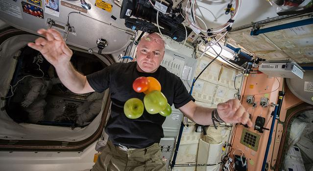 An astronaut poses with a bunch of fruit floating in front of him on the International Space Station