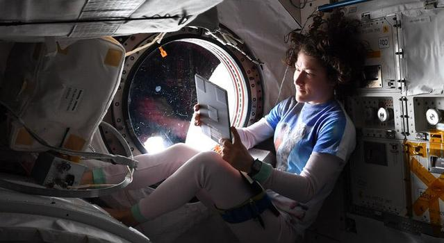 An astronaut looks at her iPad as she relaxes in her bed