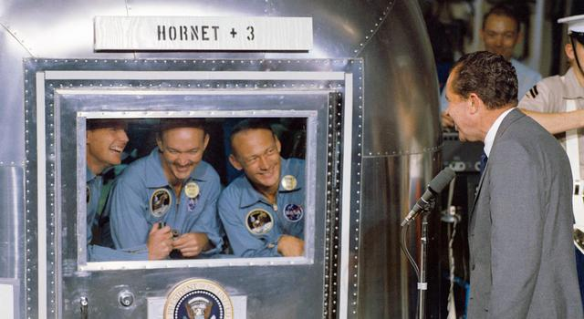 Apollo 11 astronauts stand inside a silver quarantine enclosure while then President Nixon talks to them from the outside.
