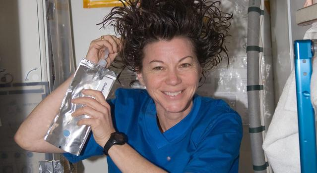 An astronaut holds a pouch of water and squeezes it into her hair to shower on the International Space Station.