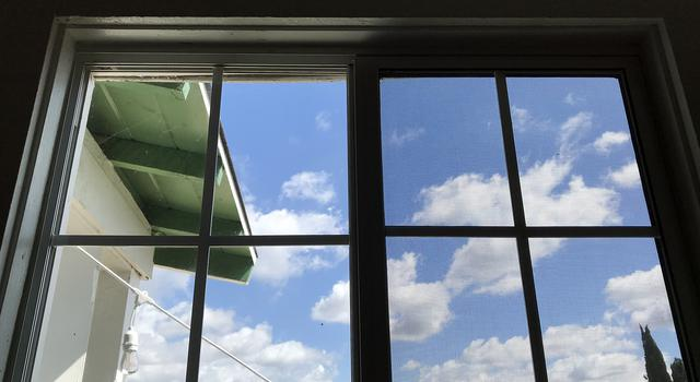 A view through a window of a blue sky with puffy clouds