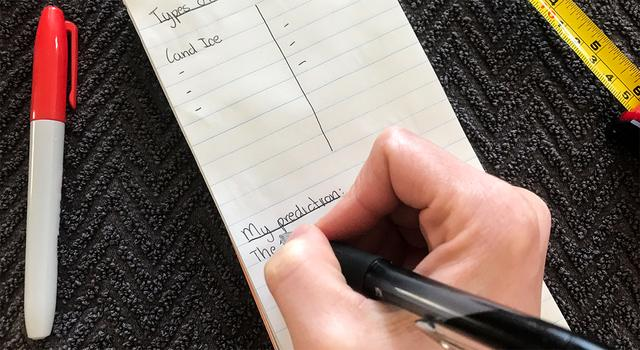 Person writing down their prediction on a notepad