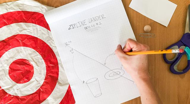 A person sketches a design for their zipline lander on a piece of graph paper with various materials spread around them