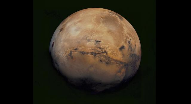 A dusty red and tan Mars and its Valles Marineris canyon system appear in striking detail in this image mosaic