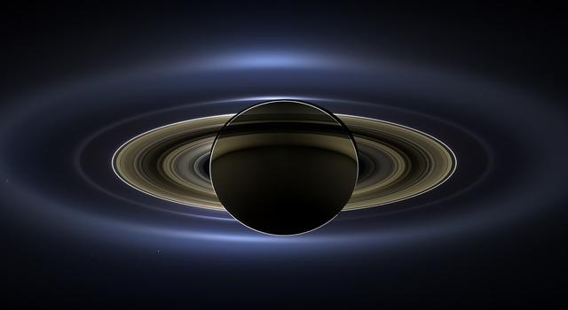 An image of Saturn lit up from behind by the Sun with the planet's moons, Earth and Mars visible as tiny specs of light in the background..