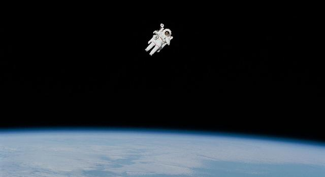 An astronaut floats in the black of space just above Earth's horizon.
