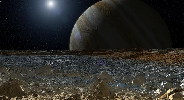 Jupiter takes up most of the sky beyond the blue and brown horizon of Europa's icy surface in this simulated view from Jupiter's moon.