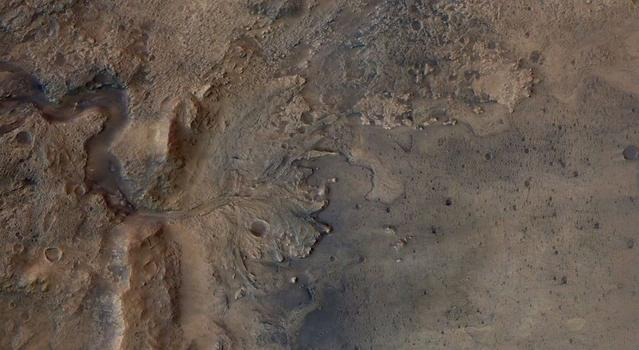 Overhead view of a large crater in a dark brown-red terrain with a deep snake-like channel leading into it.