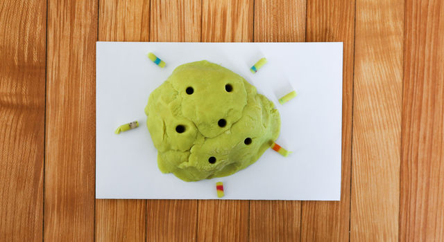 A green play dough rock is shown with multiple cores taken out of it and sitting next to it on a table.