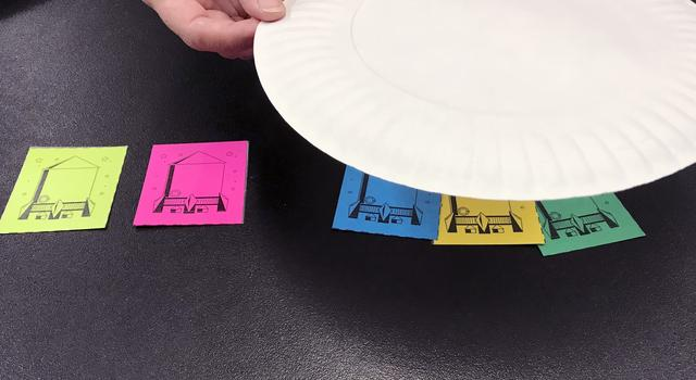 Three rocket cutouts under a paper plate, two out from under the plate