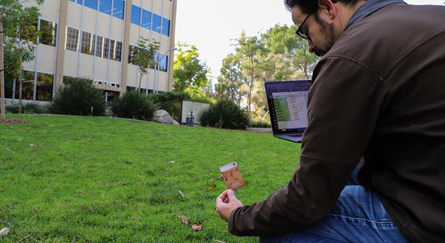 A man holds a computer with a spreadsheet of scale distances to the planets and places a Mars marker in the grass.