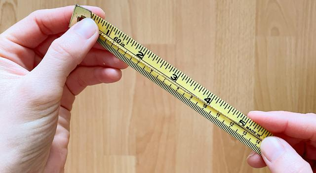 A person holds a gold string across yellow measuring tape