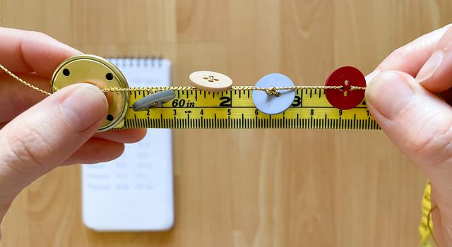 A person holds with buttons of different sizes and colors tied to it across yellow measuring tape