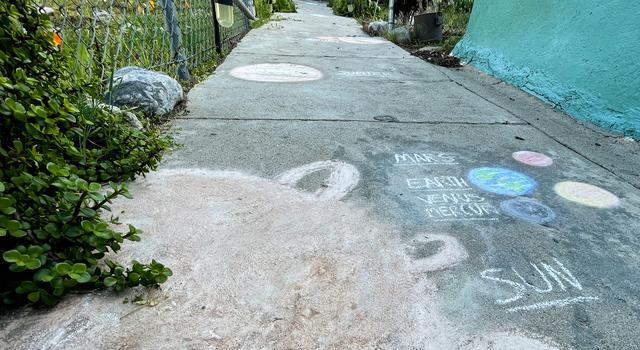 The Sun and planets drawn in chalk extend up a concrete walkway