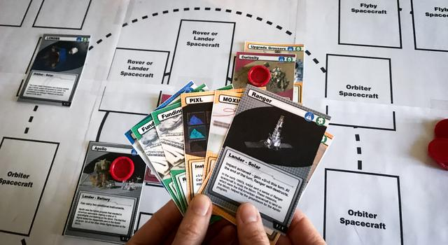 A person holds seven cards over the Space Voyagers game mat.