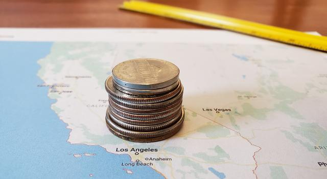 A higher stack of coins is shown on top of a printed map of the Los Angeles area