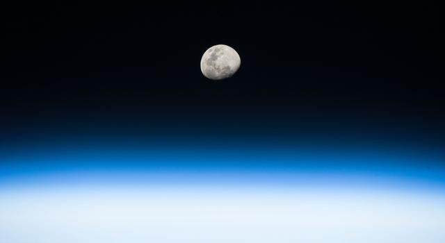 The Moon is shown beyond hazy bands of white and blue from the limb of Earth's horizon.