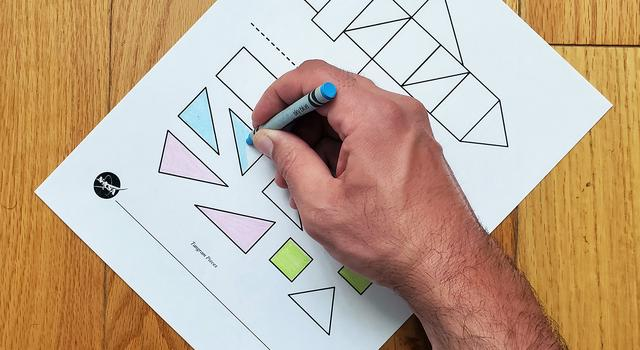A photo of a person coloring in the shapes on their rocket template