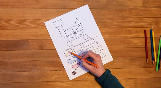 A person colors in the shapes on the tangram rover worksheet