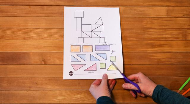 A person cuts out the shapes from the tangram rover worksheet.