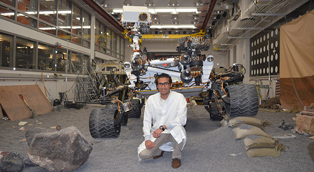 Payam Banazadeh poses with the Engineering Design Unit test-model of the Curiosity rover