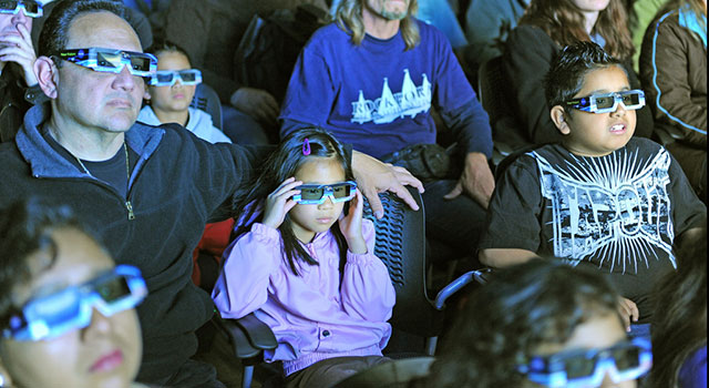 Kids and adults wearing 3D glasses sit in a theater