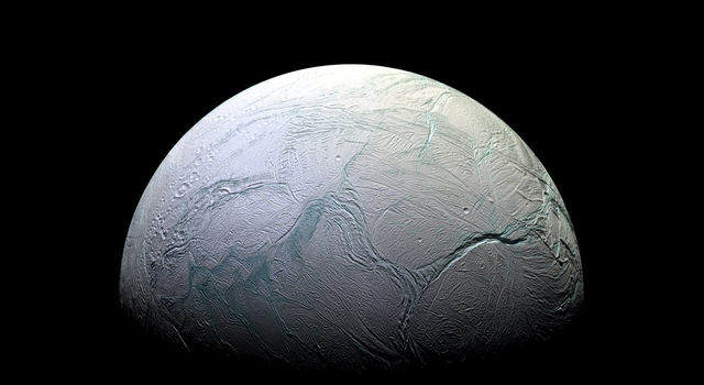 Image of Saturn's moon Enceladus covered in ice with giant cracks scarring its surface