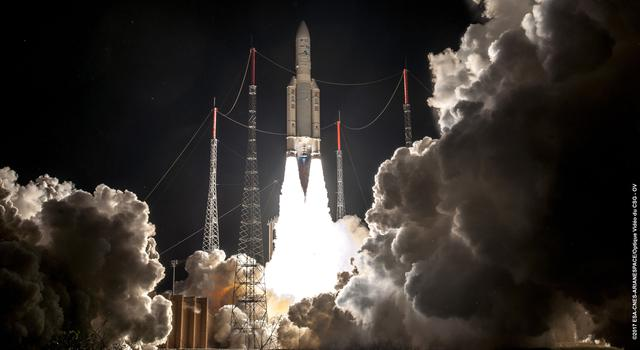 An Ariane 5 rocket is shown leaving the launch pad with puffy clouds of exhaust all around.