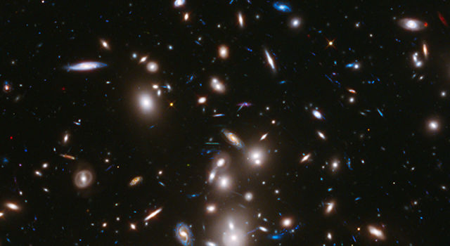 Image of bright saucer-shape galaxies dotting the blackness of space