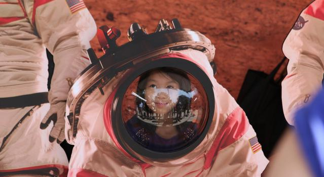 Girl looking through a Mars astronaut cutout at Explore JPL